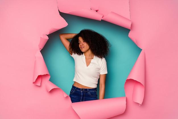 Jovem mulher afro-americana em papel rasgado, isolado em um fundo azul, tocando a parte de trás da cabeça, pensando e fazendo uma escolha.