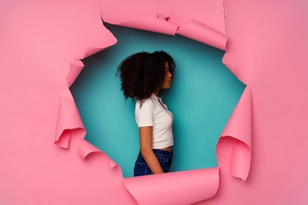 Jovem mulher afro-americana em papel rasgado, isolado no fundo azul, olhando para a esquerda, pose de lado.
