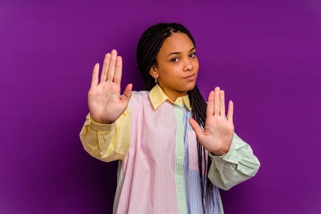 Jovem mulher afro-americana em pé com a mão estendida, mostrando o sinal de pare, impedindo você.