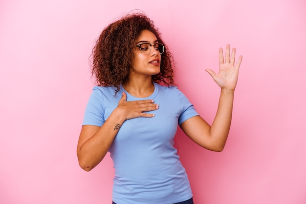 Jovem mulher afro-americana em rosa fazendo um juramento, colocando a mão no peito.
