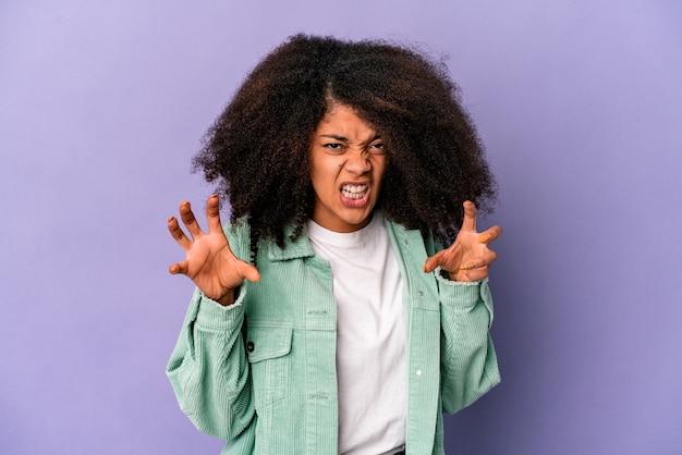 Jovem mulher afro-americana encaracolada em roxo mostrando garras imitando um gato, gesto agressivo.