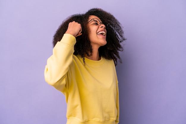 Jovem mulher afro-americana encaracolada isolada no fundo roxo, comemorando uma vitória, paixão e entusiasmo, expressão feliz.