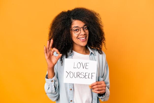 Jovem mulher afro-americana encaracolada segurando um cartaz de amor a si mesmo, alegre e confiante, mostrando o gesto de ok.