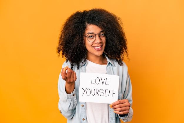 Jovem mulher afro-americana encaracolada segurando um cartaz de amor a si mesmo apontando com o dedo para você como se estivesse convidando a se aproximar.