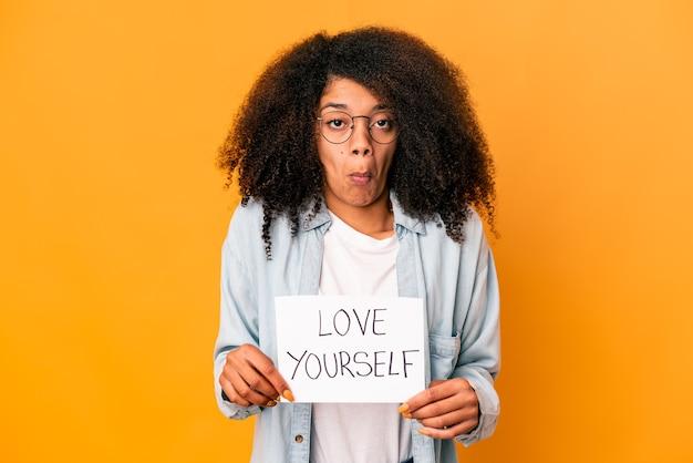 Jovem mulher afro-americana encaracolada segurando um cartaz de amor a si mesmo encolhe os ombros e abre os olhos confusos.
