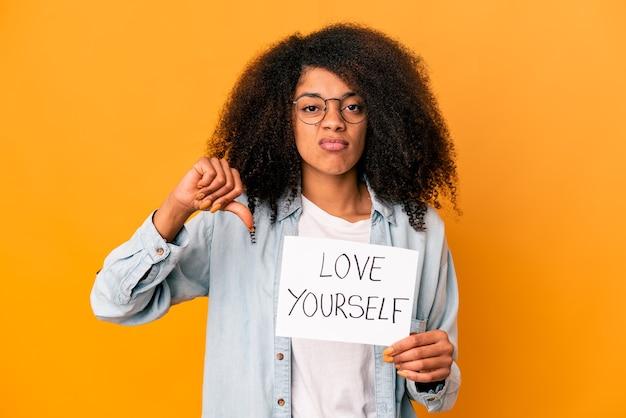 Jovem mulher afro-americana encaracolada segurando um cartaz de amor a si mesmo, mostrando um gesto de antipatia, polegares para baixo. conceito de desacordo.