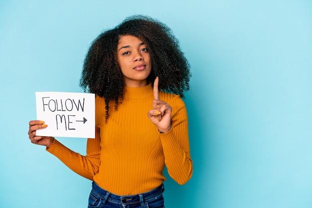 Jovem mulher afro-americana encaracolada segurando um cartaz de siga-me mostrando o número um com o dedo.