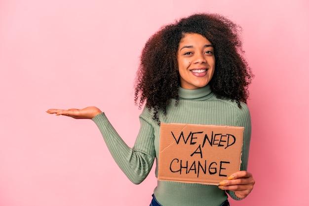 Jovem mulher afro-americana encaracolada segurando um precisamos de um cartão de mudança mostrando um espaço de cópia na palma da mão e segurando a outra mão na cintura.