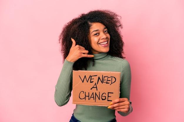 Jovem mulher afro-americana encaracolada segurando um precisamos de um cartão de mudança, mostrando um gesto de chamada de telefone móvel com os dedos.
