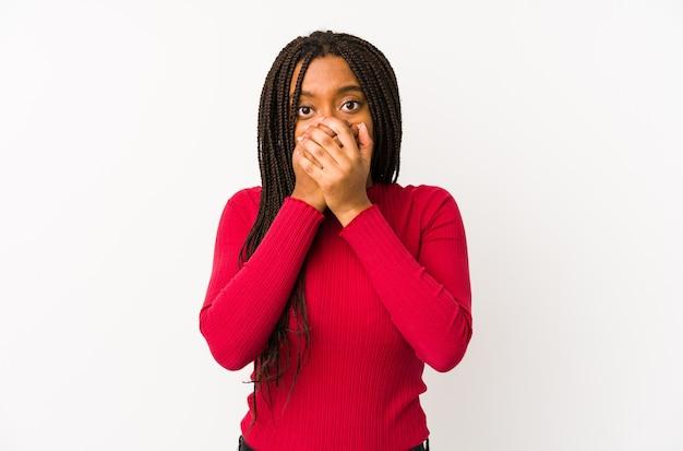 Jovem mulher afro-americana isolada chocada cobrindo a boca com as mãos.