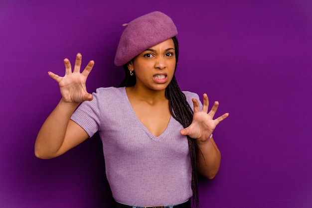 Jovem mulher afro-americana isolada em amarelo mostrando garras imitando um gato, gesto agressivo.