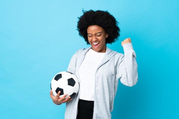 Jovem mulher afro-americana isolada em azul com bola de futebol comemorando uma vitória