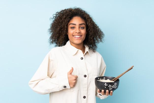 Jovem mulher afro-americana isolada em azul com polegares para cima, porque algo de bom aconteceu enquanto segura uma tigela de macarrão com pauzinhos