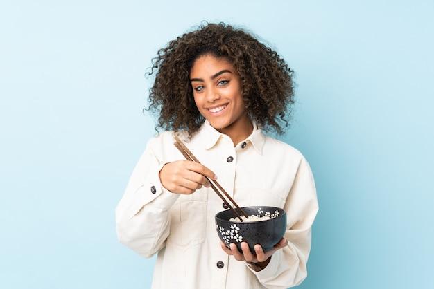Jovem mulher afro-americana isolada em azul, segurando uma tigela de macarrão com pauzinhos