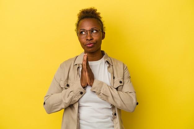 Jovem mulher afro-americana isolada em fundo amarelo orando, mostrando devoção, pessoa religiosa em busca de inspiração divina.