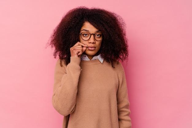Jovem mulher afro-americana isolada em rosa com os dedos nos lábios, mantendo um segredo.