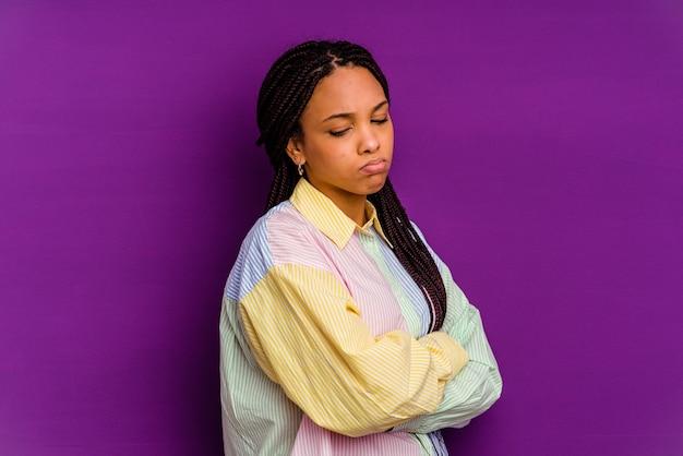 Jovem mulher afro-americana isolada em um fundo amarelo, cansada de uma tarefa repetitiva.