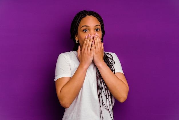 Jovem mulher afro-americana isolada em um fundo amarelo chocada, cobrindo a boca com as mãos, ansiosa para descobrir algo novo.
