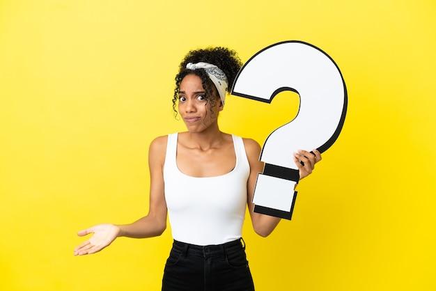 Jovem mulher afro-americana isolada em um fundo amarelo segurando um ícone de ponto de interrogação e tendo dúvidas