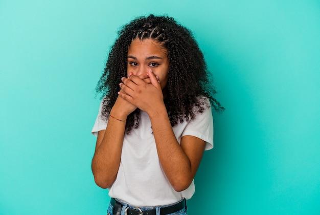 Jovem mulher afro-americana isolada em um fundo azul, cobrindo a boca com as mãos parecendo preocupadas.