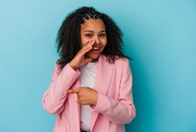 Jovem mulher afro-americana isolada em um fundo azul, dizendo uma fofoca, apontando para o lado relatando algo.