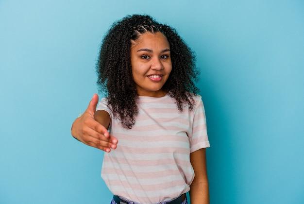Jovem mulher afro-americana isolada em um fundo azul, esticando a mão na câmera em um gesto de saudação.
