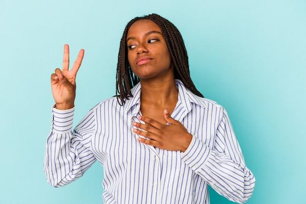Jovem mulher afro-americana isolada em um fundo azul, fazendo um juramento, colocando a mão no peito.