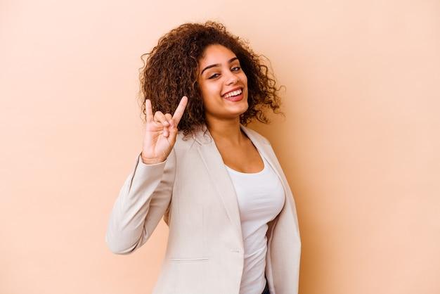 Jovem mulher afro-americana isolada em um fundo bege, mostrando um gesto de chifres como um conceito de revolução.