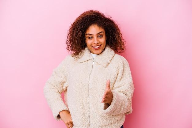 Jovem mulher afro-americana isolada em um fundo rosa, esticando a mão na câmera em um gesto de saudação.