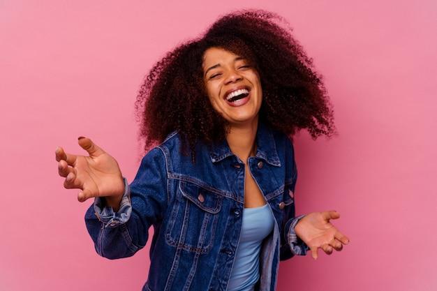 Jovem mulher afro-americana isolada em um fundo rosa se sente confiante em dar um abraço para a câmera.