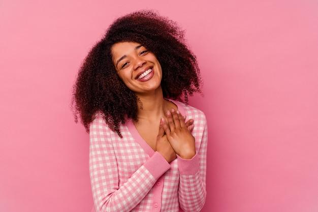 Jovem mulher afro-americana isolada em um fundo rosa tem uma expressão amigável, pressionando a palma da mão no peito. conceito de amor.