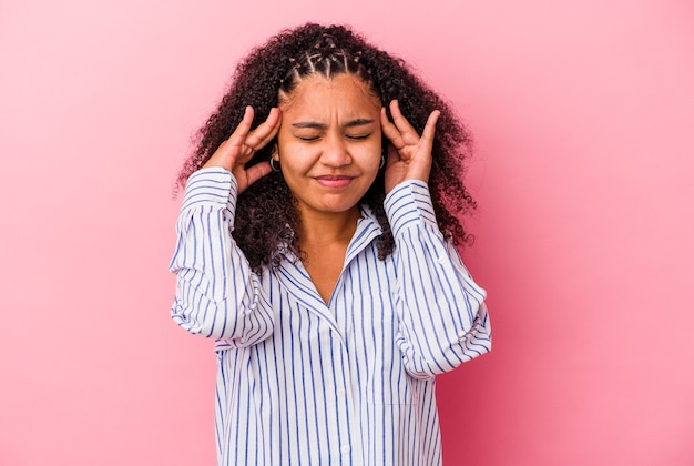 Jovem mulher afro-americana isolada em um fundo rosa, tocando as têmporas e tendo dor de cabeça.