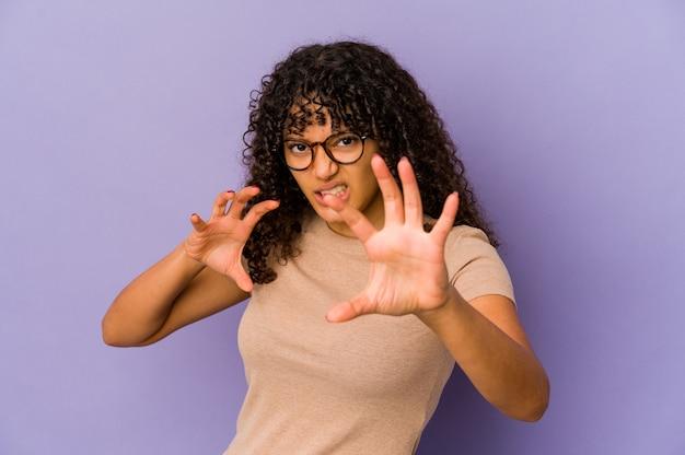 Jovem mulher afro-americana isolada mostrando garras imitando um gato, gesto agressivo.