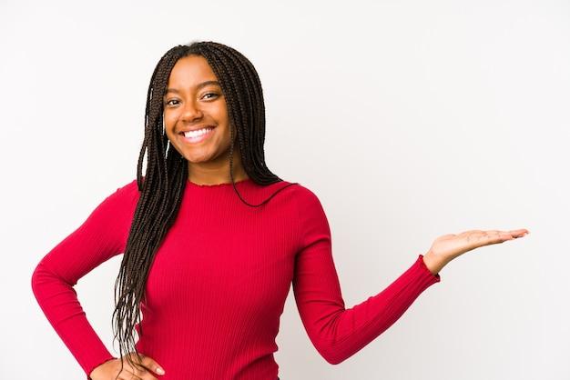 Jovem mulher afro-americana isolada, mostrando um espaço de cópia na palma da mão e segurando a outra mão na cintura.
