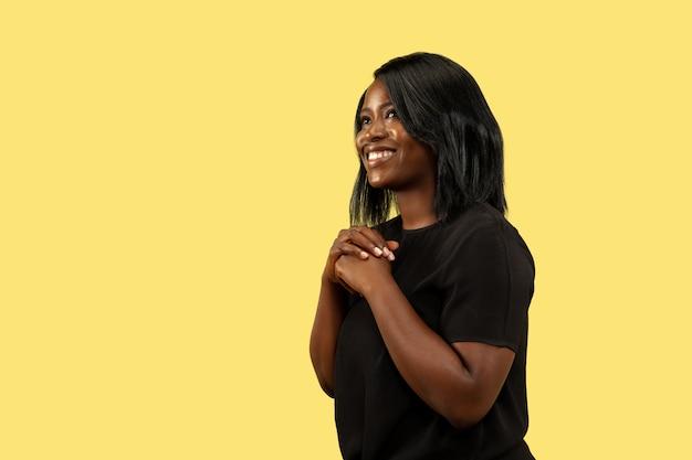 Jovem mulher afro-americana isolada na parede amarela, expressão facial. belo retrato feminino de meio corpo. conceito de emoções humanas, expressão facial. de pé e sorrindo.