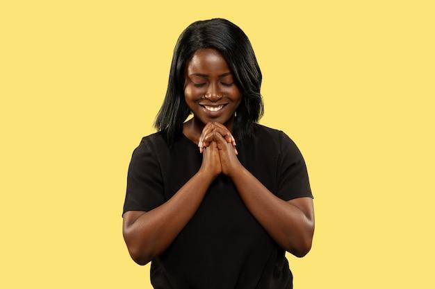 Jovem mulher afro-americana isolada na parede amarela, expressão facial. belo retrato feminino de meio corpo. conceito de emoções humanas, expressão facial. rezando e sorrindo.