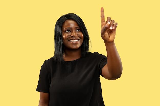 Jovem mulher afro-americana isolada na parede amarela, expressão facial. belo retrato feminino de meio corpo. conceito de emoções humanas, expressão facial. tocando em uma barra de pesquisa vazia.