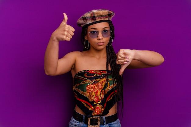 Jovem mulher afro-americana isolada na parede amarela mostrando os polegares para cima e para baixo, é difícil escolher o conceito