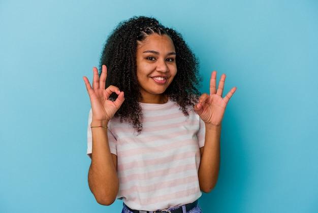 Jovem mulher afro-americana isolada na parede azul alegre e confiante, mostrando um gesto de ok.