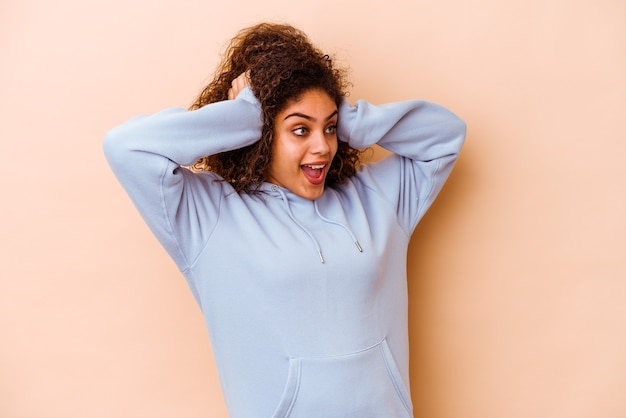 Jovem mulher afro-americana isolada na parede bege, gritando, muito animada, apaixonada, satisfeita com alguma coisa.