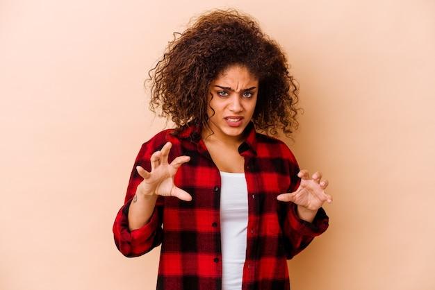 Jovem mulher afro-americana isolada na parede bege, mostrando garras imitando um gato, gesto agressivo.