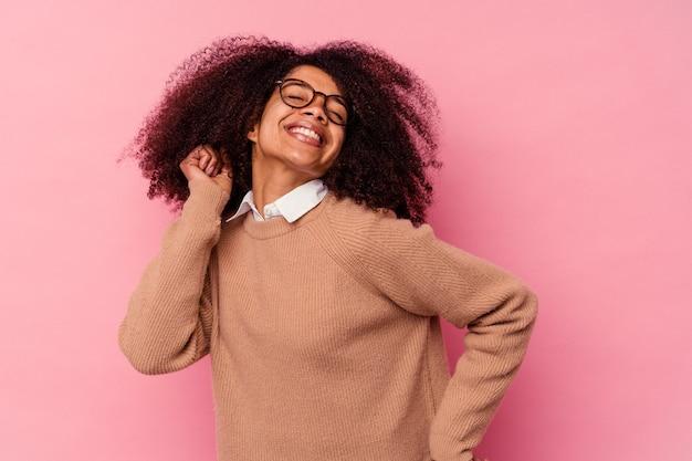 Jovem mulher afro-americana isolada na parede rosa, dançando e se divertindo.