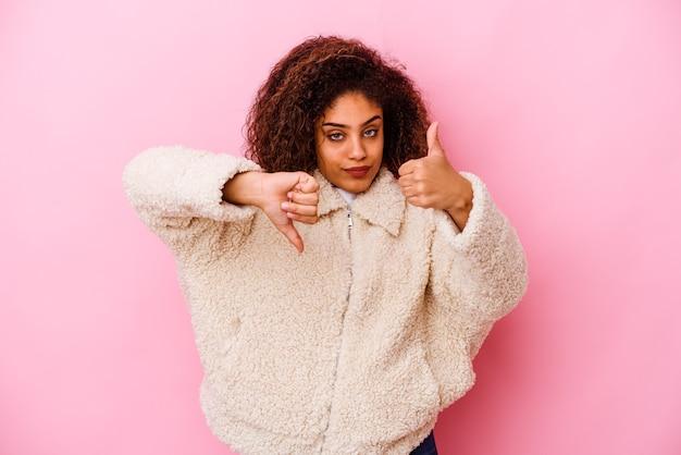 Jovem mulher afro-americana isolada na parede rosa mostrando os polegares para cima e para baixo, é difícil escolher o conceito