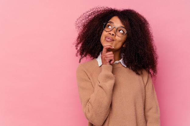 Jovem mulher afro-americana isolada na parede rosa, olhando de soslaio com expressão duvidosa e cética.