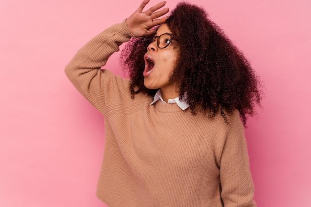 Jovem mulher afro-americana isolada na rosa, olhando para longe, mantendo a mão na testa.