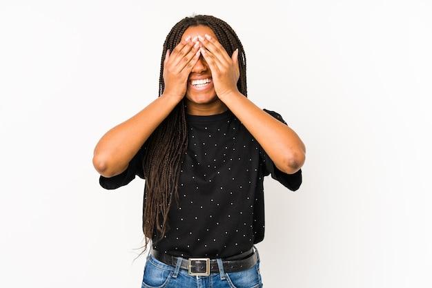 Jovem mulher afro-americana isolada no branco cobre os olhos com as mãos, amplamente à espera de uma surpresa.