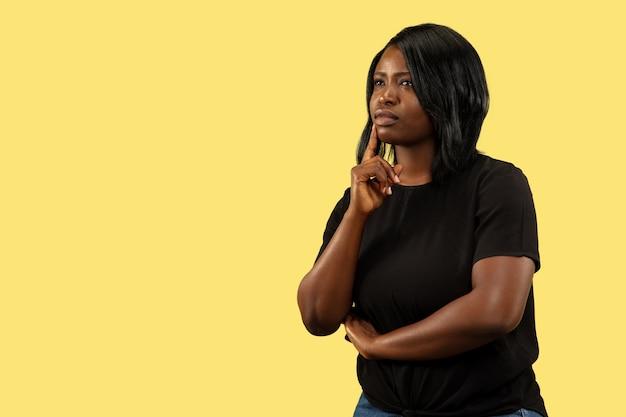 Jovem mulher afro-americana isolada no espaço amarelo, expressão facial. belo retrato feminino de meio corpo.