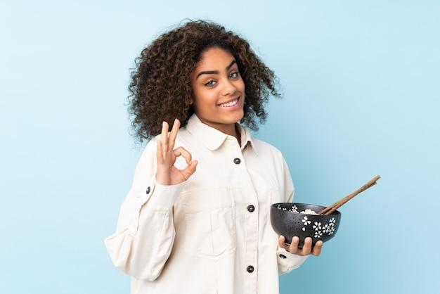 Jovem mulher afro-americana isolada no espaço azul, mostrando sinal de ok com os dedos, mantendo uma tigela de macarrão com pauzinhos