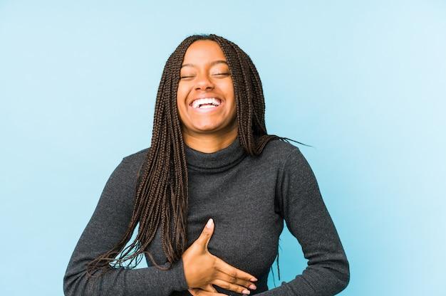 Jovem mulher afro-americana isolada no espaço azul ri alegremente e se diverte mantendo as mãos na barriga.