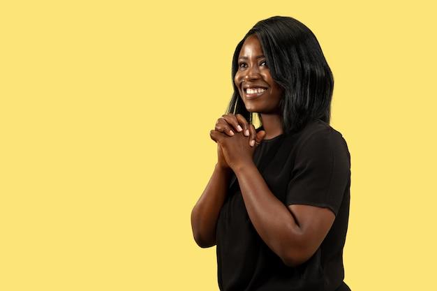 Jovem mulher afro-americana isolada no fundo amarelo do estúdio, expressão facial. belo retrato feminino de meio corpo. conceito de emoções humanas, expressão facial. de pé e sorrindo.